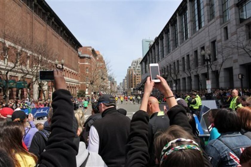 In this Monday, April 15, 2013, photo, spectators make pictures with camera phones during the Boston Marathon in Boston, before two bombs exploded at the finish line in an attack that killed 3 people and wounded over 170. As the investigation of the Boston Marathon bombings illustrates, getting los