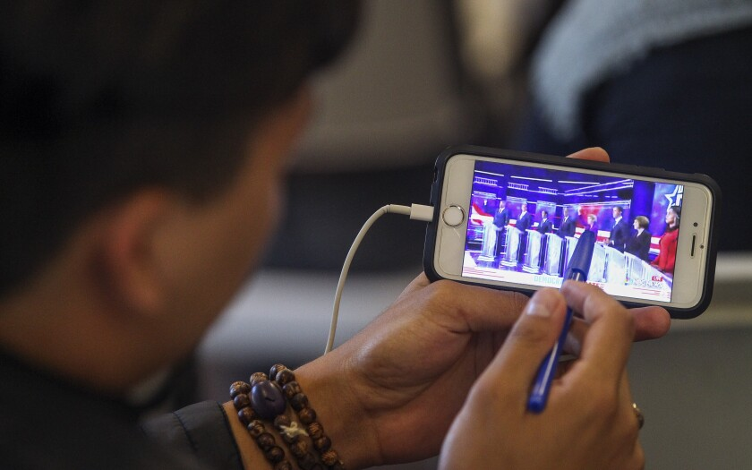 Ryan Roden, 19, a UCSD student, watches  the Democratic presidential debate on his phone during a watch party, put on by Youth Will, at the Jacobs Center For Neighborhood Innovation on Wednesday, June 26, 2019 in San Diego, California.