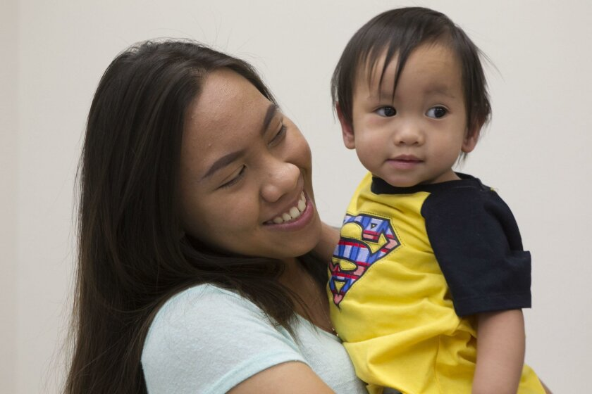 Queeffer Leomo holds her 11-month-old brother, Zey, at Rady Children's Hospital.