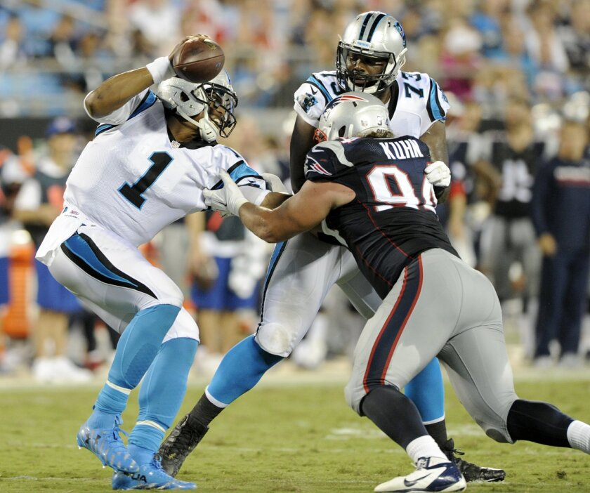 Carolina Panthers' Cam Newton (1) tries to escape the grasp of New England Patriots' Markus Kuhn (94) during the second half of a preseason NFL football game in Charlotte, N.C., Friday, Aug. 26, 2016. (AP Photo/Mike McCarn)