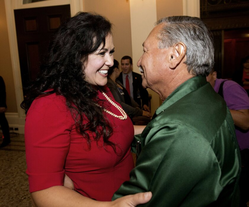 Assemblywoman Lorena Gonzalez, D-San Diego, receives congratulations from Arturo Rodriguez, president of the United Farm Workers, after the Assembly approved her bill requiring farmworkers to receive overtime pay after working eight hours, at the Capitol, in Sacramento, Calif. Calif. Gov. Jerry Bro