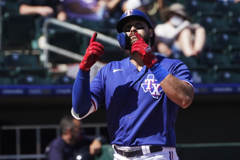 Texas Rangers' Joey Gallo gestures as he crosses home plate on a home run during the first inning of the team's spring training baseball game against the Cleveland Indians, Tuesday, March 9, 2021, in Surprise, Ariz. (AP Photo/Sue Ogrocki)