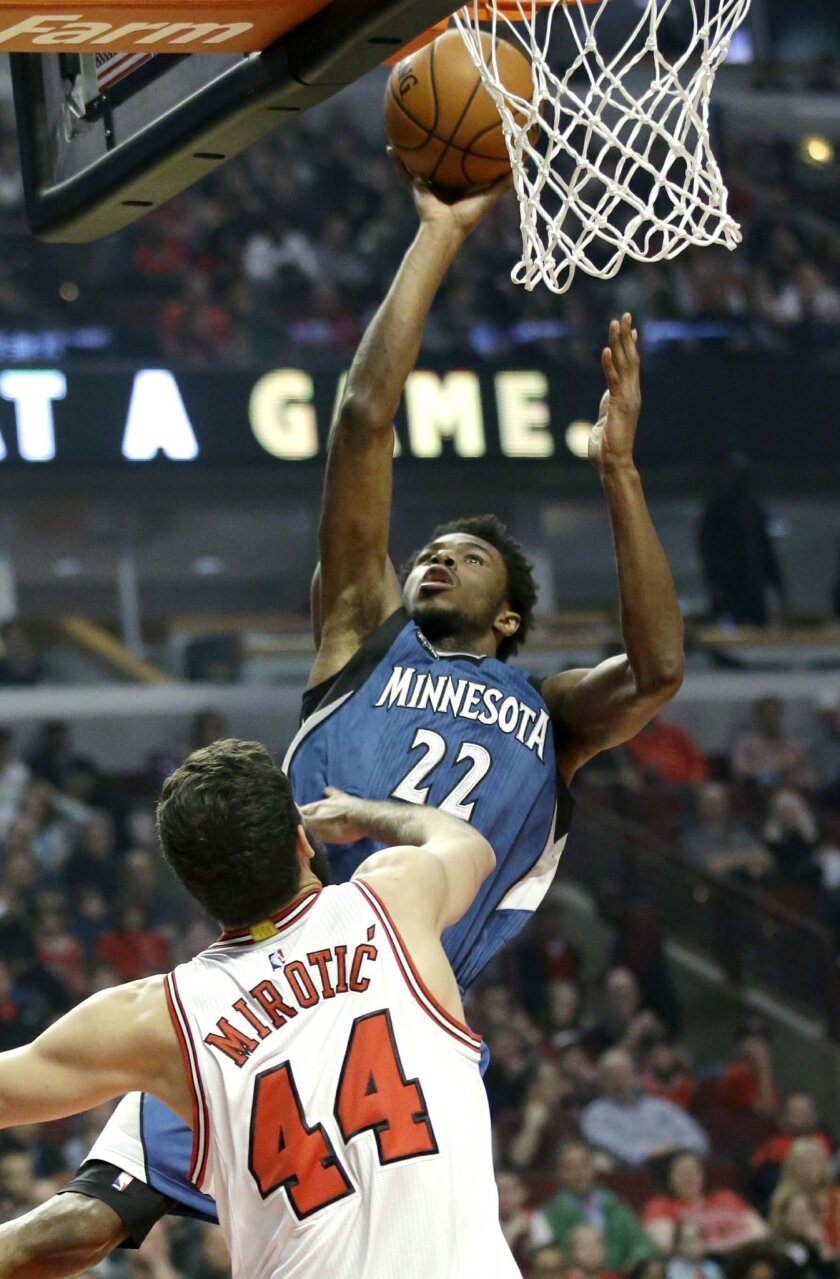 Minnesota Timberwolves guard/forward Andrew Wiggins, top, drives to the basket against Chicago Bulls forward Nikola Mirotic during the first half of an NBA basketball game on Saturday, Nov. 7, 2015,  in Chicago. (AP Photo/Nam Y. Huh)