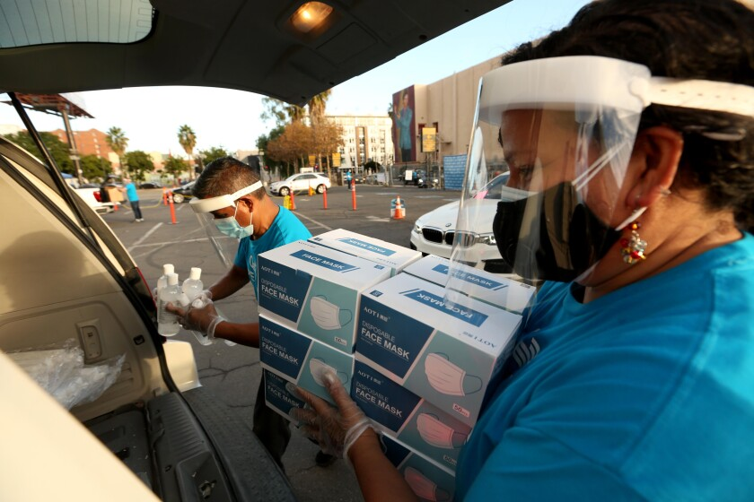Two people load boxes of masks and hand sanitizer into a car.