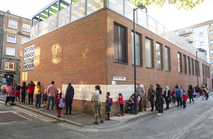Pupils and parents queue on the first day back to school at Charles Dickens Primary School in London, Tuesday Sept. 1, 2020. Hundreds of thousands of British schoolchildren are heading back to classrooms, with the country watching nervously to see if reopening schools brings a surge in coronavirus infections. Tuesday marks the start of term for about 40% of schools in England and Wales, with the rest reopening in the coming days. (Dominic Lipinski/PA via AP)