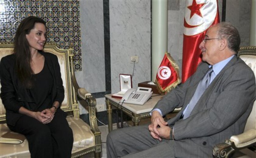 U.S. actress and United Nations High Commissioner for Refugee goodwill ambassador Angelina Jolie, left, talks with Tunisian Foreign Minister Mouldi Kefi, Wednesday April, 6, 2011 in Tunis. Jolie traveled on Tuesday morning to the Tunisian-Libyan border to urge greater international support for people fleeing Libya. (AP Photo)