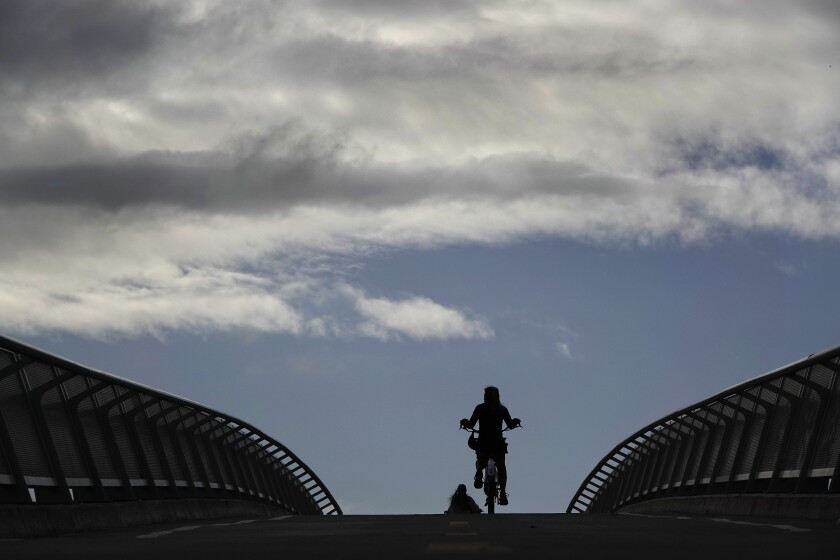 People ride bikes on the Mike Gotch Memorial Bridge across the Rose Canyon Creek.