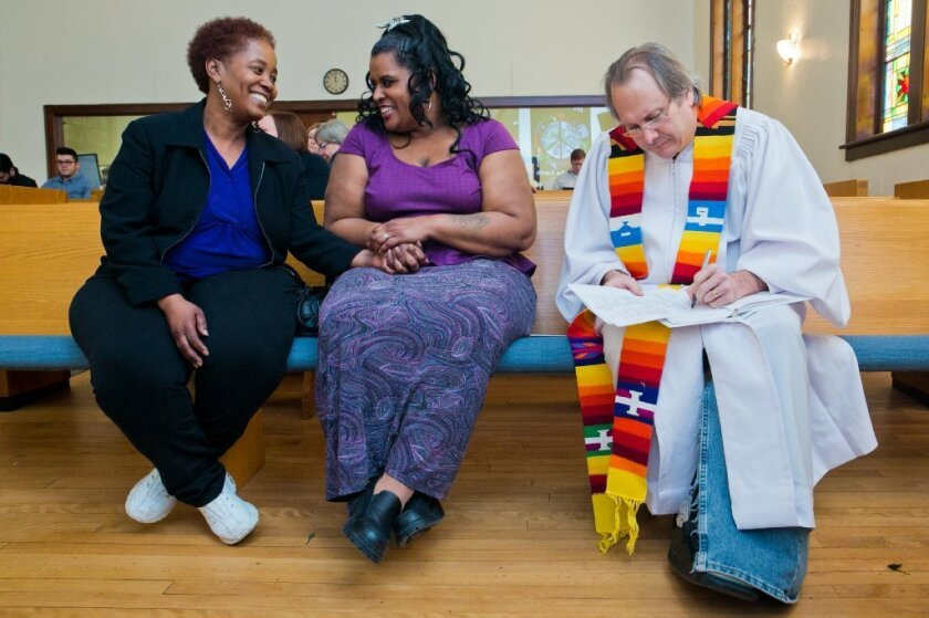 Renecia Hall, left, and Kristen Martin wait for their marriage license from Rev. Bill Freeman at Harbor Unitarian Universalist church in Muskegon, Mich., in March.