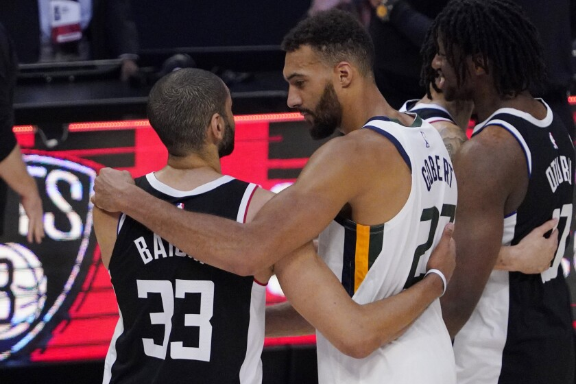 Los Angeles Clippers forward Nicolas Batum, left, of France talks with Utah Jazz center Rudy Gobert, of France, after the Clippers defeated the Jazz 131-119 in Game 6 of a second-round NBA basketball playoff series Friday, June 18, 2021, in Los Angeles. (AP Photo/Mark J. Terrill)