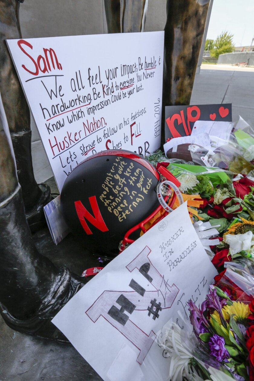 A helmet, signs and flowers are among the items Wednesday, July 27, 2016, at a makeshift memorial in Lincoln, Neb., for Nebraska college football punter Sam Foltz, who died Saturday in a Wisconsin car crash. The 22-year-old Foltz and former Michigan State punter Mike Sadler died in a single-car cra