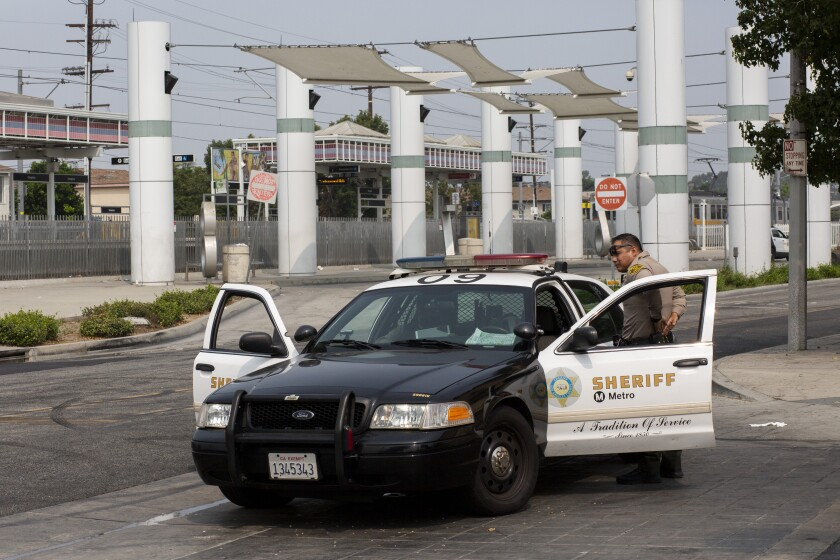 An L.A. County sheriff's deputy patrols near the Compton Metro station in the wake of deputies' shooting.