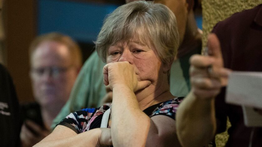 A woman listens to Matthew Weintraub, District Attorney for Bucks County, Pa., speak during a news c