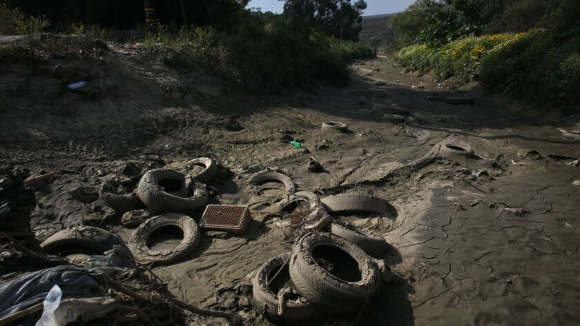 Along Monument Road in the area just north of the U.S. - Mexico border wall at Smuggler's Gulch, the northward flow of storm runoff brings piles of tires and plastic bottles and other trash as well