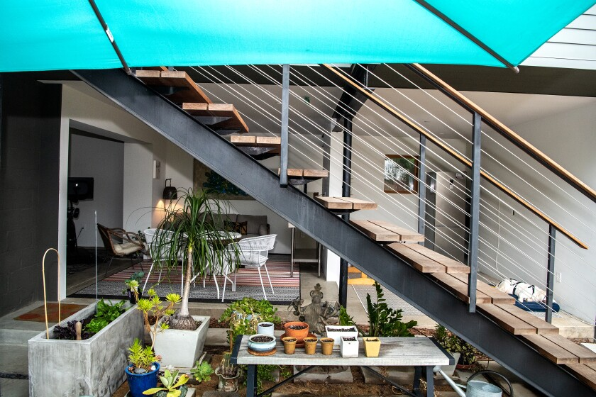 An outdoor living area is located beneath the ADU, which is accessed by stairs.