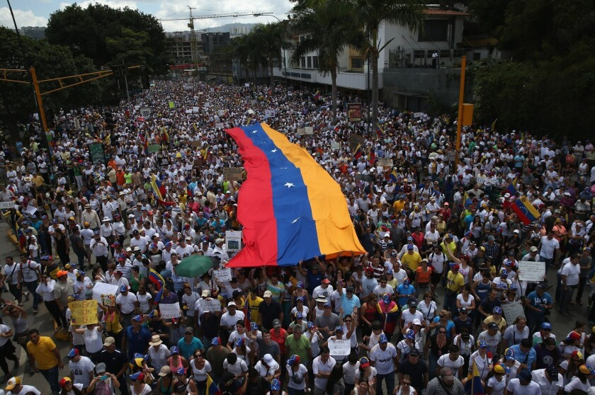 Anti-government protesters, some carrying a giant Venezuelan flag, march Sunday in Caracas, Venezuela.