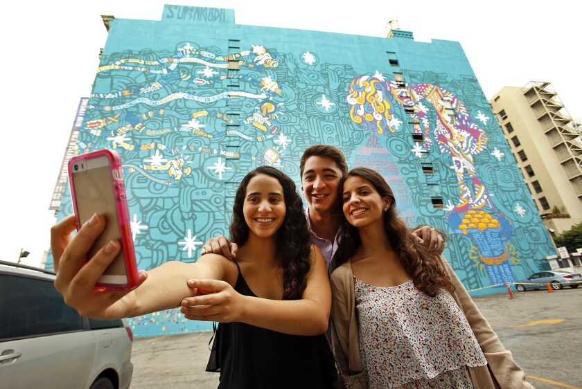 Now you can put an image of yourself on a piece of toast with a selfie toaster. Above, visitors from Mexico take a traditional selfie in front of a mural in downtown L.A.