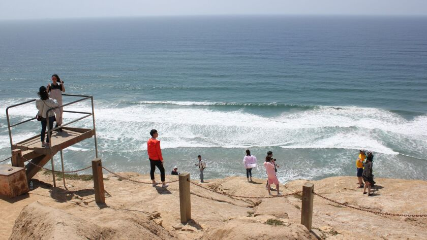Nine Torrey Pines visitors ignore City signage and shoot pictures at roped-off bluffs on April 24.