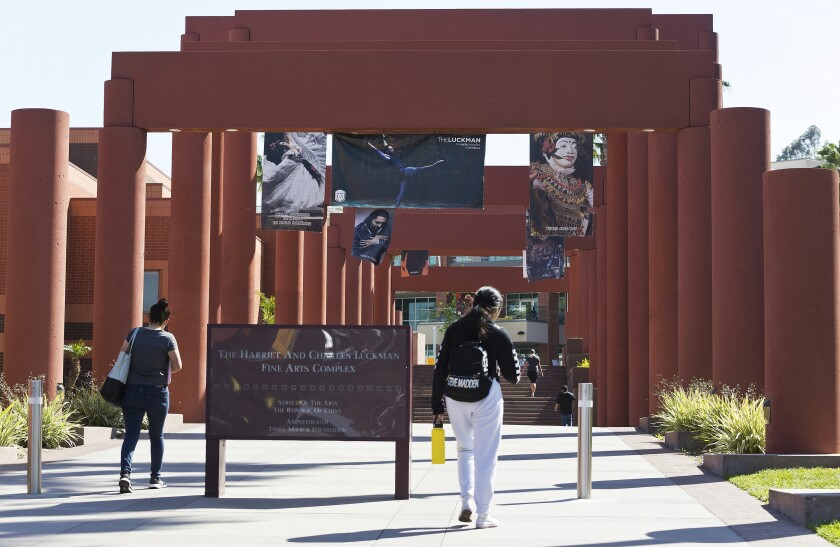 FILE - In this April 25, 2019, photo students walk past the Harriet and Charles Luckman Fine Arts Complex at the Cal State University, Los Angeles campus. Two of the nation's largest university systems say they intend to require COVID-19 vaccinations for all students, faculty and staff on University of California and California State University campuses this fall once the Food and Drug Administration gives formal approval, Thursday, April 22, 2021. (AP Photo/Damian Dovarganes, File)
