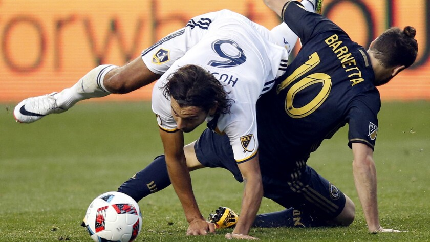Galaxy midfielder Baggio Husidic gets tangled with the Union's Tranquillo Barnetta during a game las