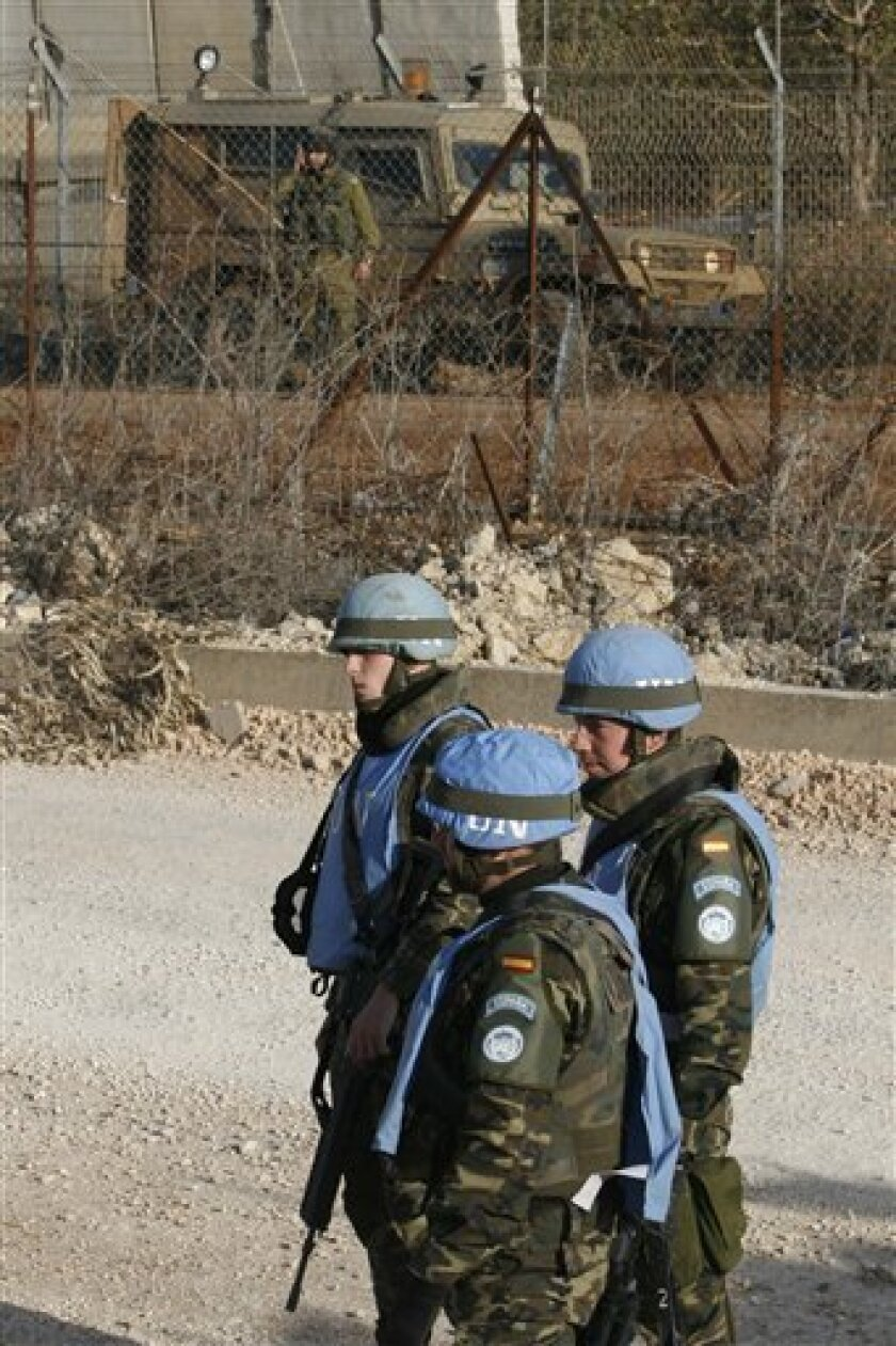 Spanish U.N peacekeeper soldiers, are seen during a patrol at the Lebanese-Israeli border in front of an Israeli army vehicle, near the Lebanese village of Kfar Kila, south of Lebanon, on Monday Jan. 5, 2009. The hilltop Israeli outpost towers over this south Lebanon village along the two countries