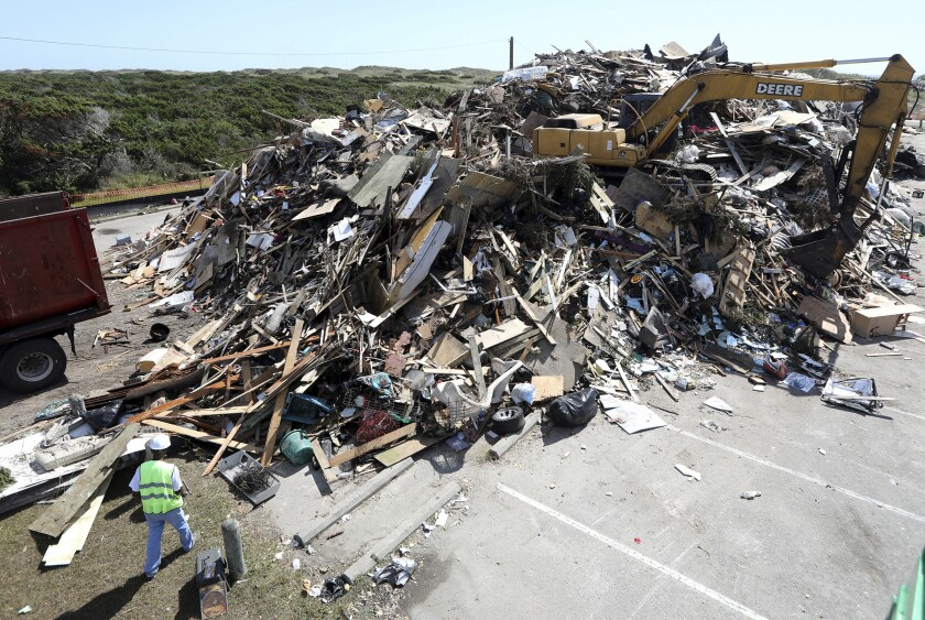 A mountain of 11,000 cubic yards of construction debris is piled in a parking lot as Ocracoke recovers from Hurricane Dorian flooding on Monday, Sept. 23, 2019. A secluded tourist destination on North Carolina's Outer Banks is having an extremely tough year. Ocracoke Island is recovering from the most damaging hurricane in its recorded history and the near-economic paralysis wrought by one of the world's worst pandemics. (Steve Earley/The Virginian-Pilot via AP)