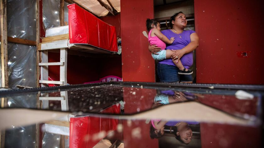 Petrona Nunez, with daughter Jazabell, 2, surveys the damage from Hurricane Irma to their home in Immokalee, Fla.