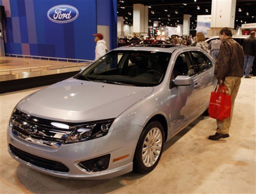 In this April 3, 2009 photo, a prospective buyer looks over the 2010 Fusion hybrid sedan on display in the Ford area at the Denver Auto Show in Denver. Ford Motor Co. says its April sales fell 32 percent, but the company gained market share on record retail sales of its midsize Ford Fusion. (AP Photo/David Zalubowski)
