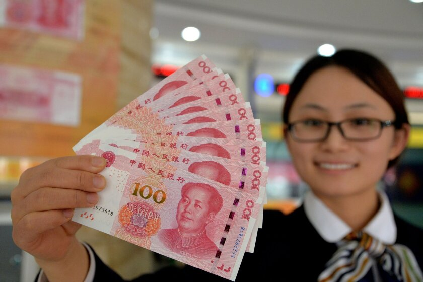 A bank employee shows new 100-yuan bank notes in Handan, in northern China's Hebei province, on Nov. 12.