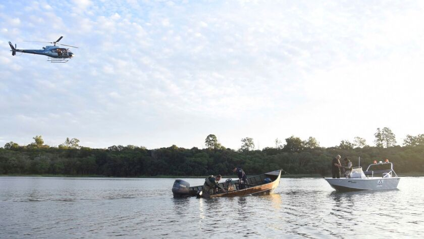 Police inspect a boat in the Parana River, on the border of Brazil and Paraguay, used by assailants