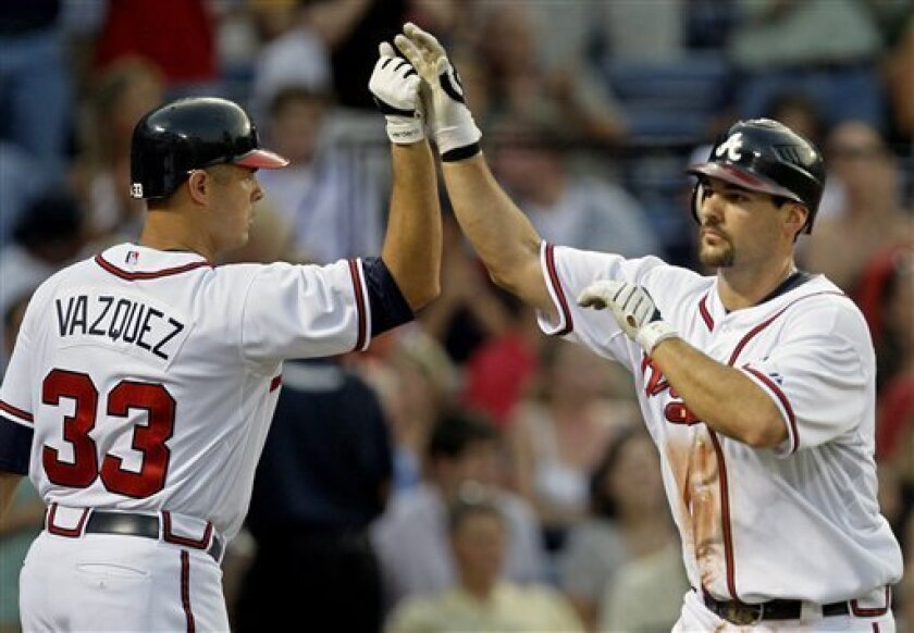 Atlanta Braves' Casey Kotchman, right, celebrates with teammate Javier Vazquez after hitting a two-run home run in the fourth inning of a baseball game against the Philadelphia Phillies in Atlanta, Thursday July 2, 2009. (AP Photo/John Bazemore)