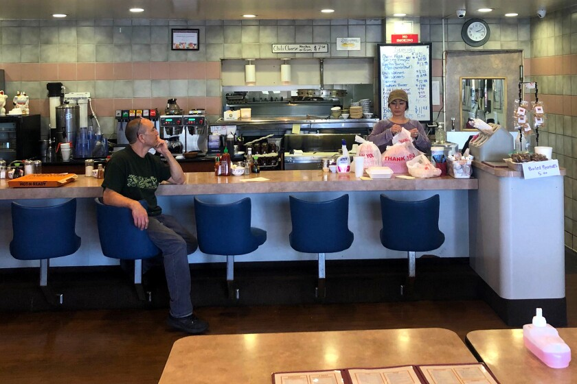 Gardena Bowl Coffee Shop co-owner Frank Nakano sits at the counter with employee Stefanie Yamasaki standing behind it.