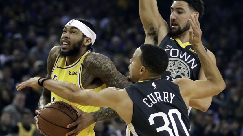 Lakers' Brandon Ingram, left, drives the ball past Golden State Warriors' Stephen Curry (30) and Klay Thompson in the first half on Saturday in Oakland.