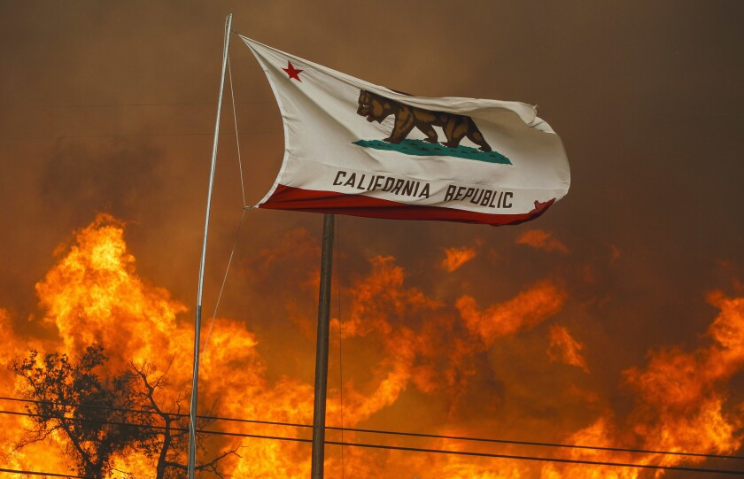The California state flag flies next to a home on Highway 94 south of Potrero on Monday as huge flames roar behind it.