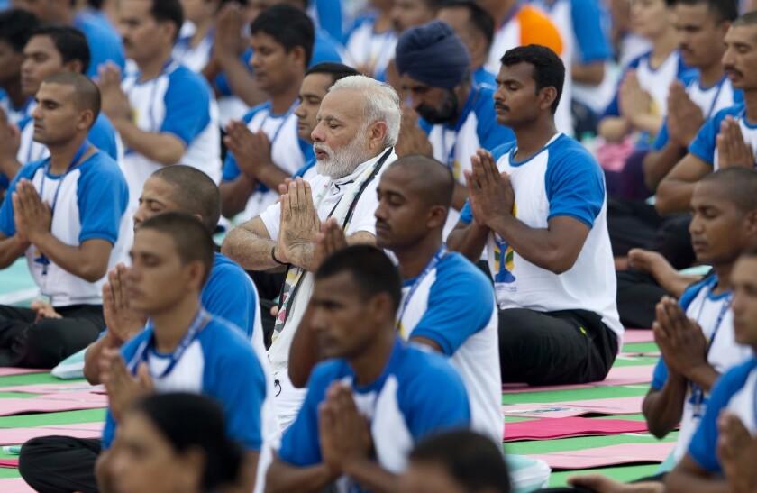 El primer ministro de India, Narendra Modi (centro), practiya yoga junto a miles de indios en Chandigarh, India. (AP Foto/Saurabh Das)