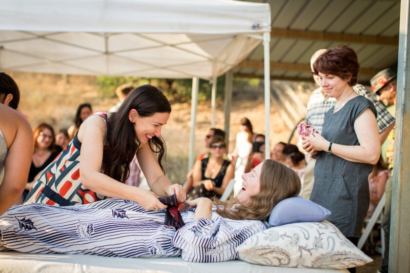 """Amanda Friedland, left, surrounded by friends and family, adjusts her friend Betsy Davis's sash as she lays on a bed during her """"Right To Die Party"""" in Ojai, Calif. Betsy's sister, Kelly, is at right."""