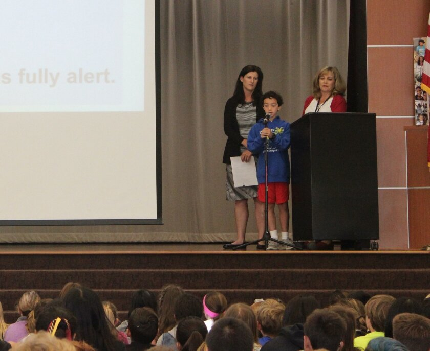 """Solana Pacific Elementary student Cole Spector makes his """"Slam ALS"""" presentation to a school assembly recently, flanked by teacher Kelly Monahan (left) and guidance counselor Lisa Burkle."""