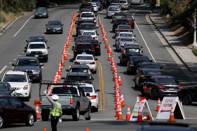 Cars line up for drive-through coronavirus testing at Dodger Stadium in Los Angeles.