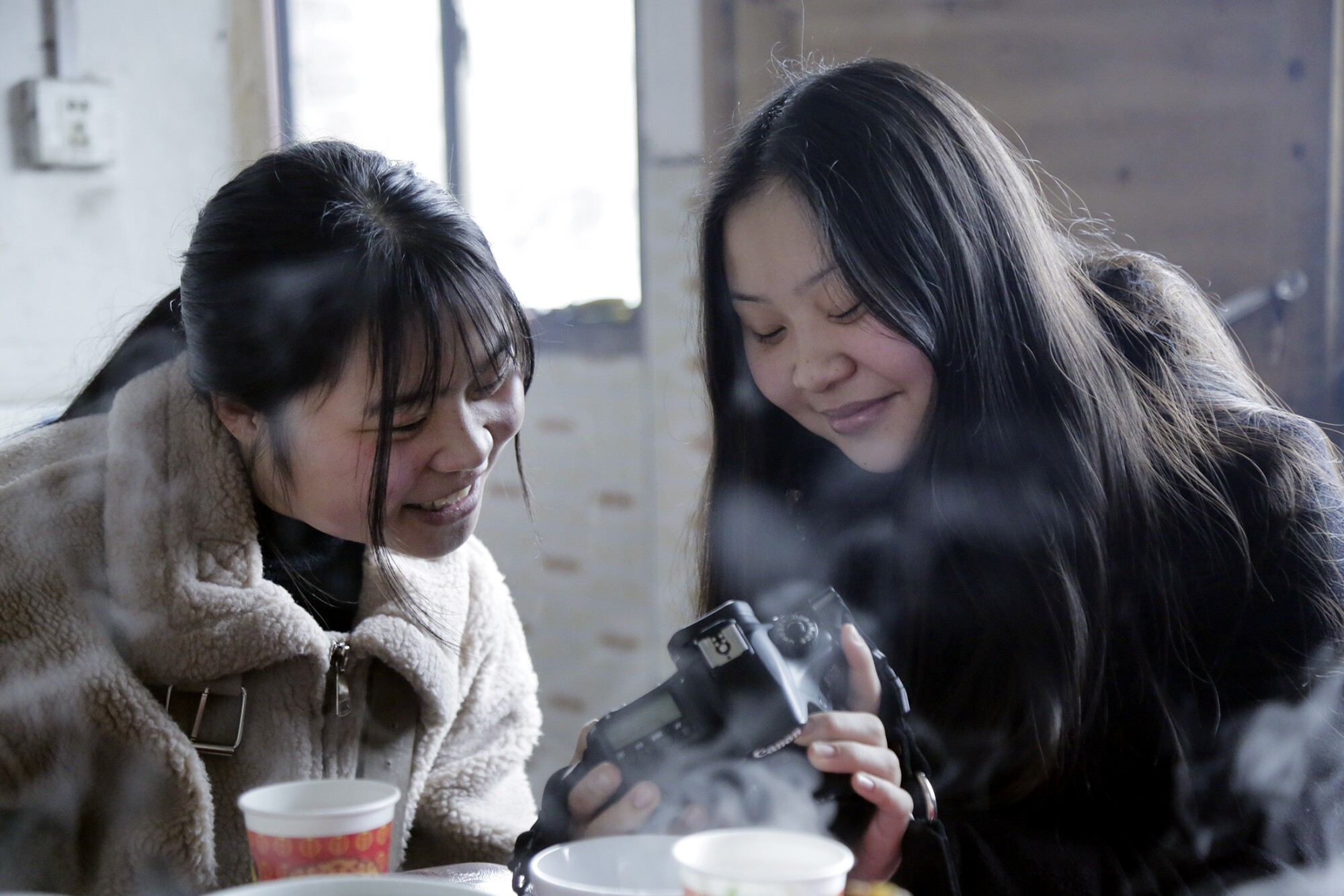 Esther Frederick shows her identical twin, Zeng Shuangjie, photos she took with her camera. Esther is interested in photography, art, baking and fashion, while Shuangjie likes badminton, pingpong, music and writing Chinese characters. The girls were separated when they were toddlers.