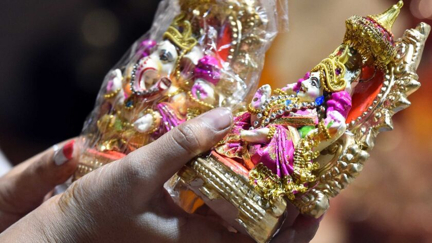 People buy idols of Goddess Lakshmi and Lord Ganesha from roadside stalls for the Diwali festival in New Delhi.