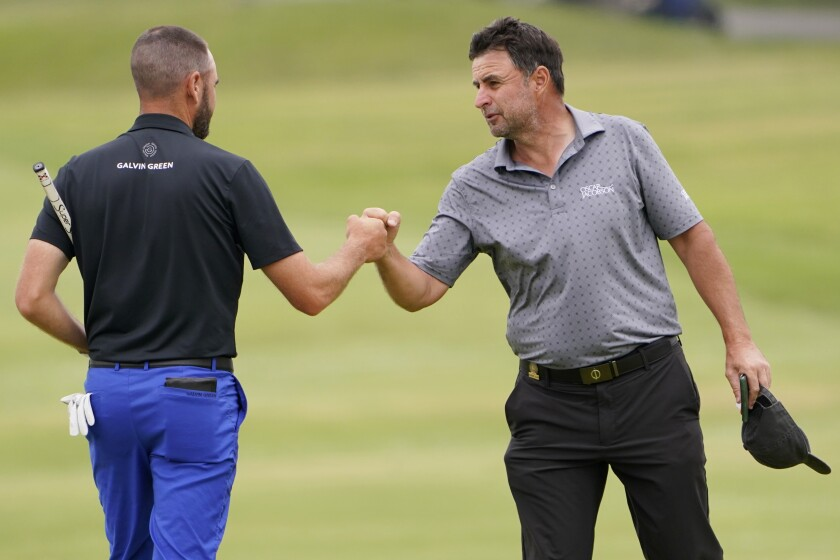 Richard Bland, of England, right, fist bumps Troy Merritt after their round on the ninth green during the second round of the U.S. Open Golf Championship, Friday, June 18, 2021, at Torrey Pines Golf Course in San Diego. (AP Photo/Jae C. Hong)