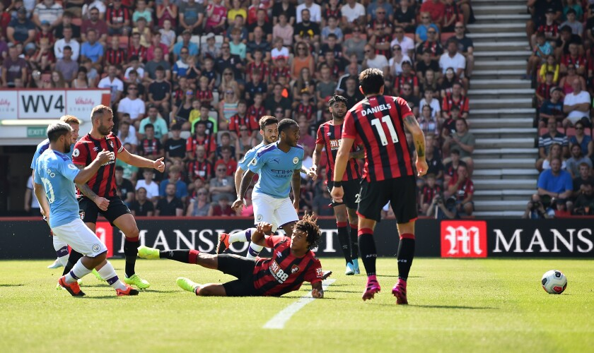Manchester City's Argentinian striker Sergio Aguero, left, scores against Bournemouth on Aug. 25.