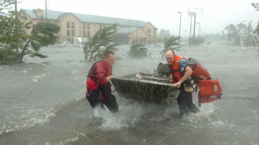 Fire and rescue personnel head out to save a family trapped by Hurricane Katrina in Pascagoula, Miss.