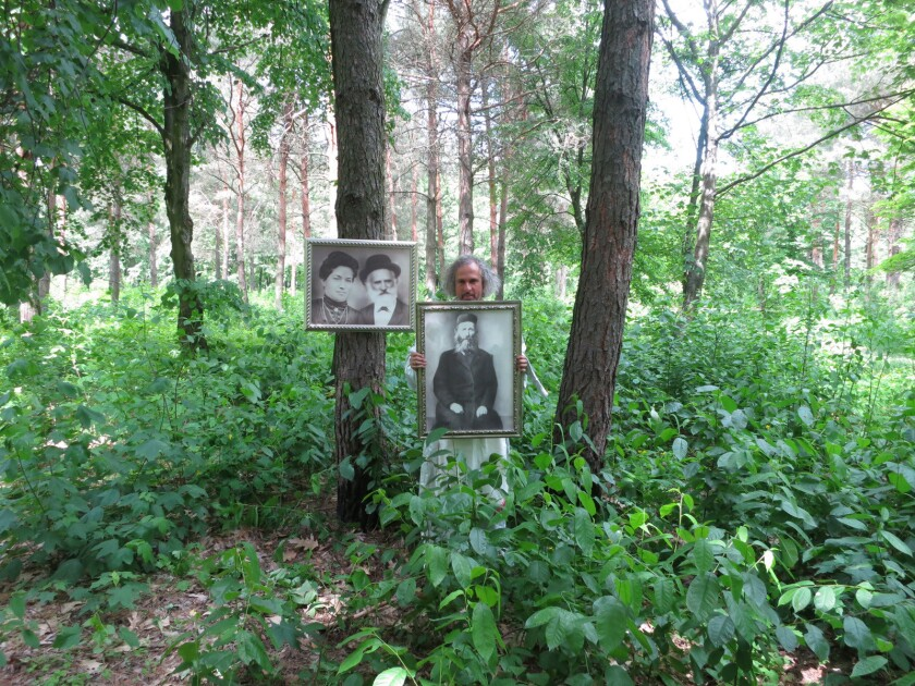 Artist Gary Baseman is at work on a film that will tell the story of how his parents, Eastern European Jews, survived World War II. Here the artist stands with photos of his grandparents in Berezne, his father's hometown.