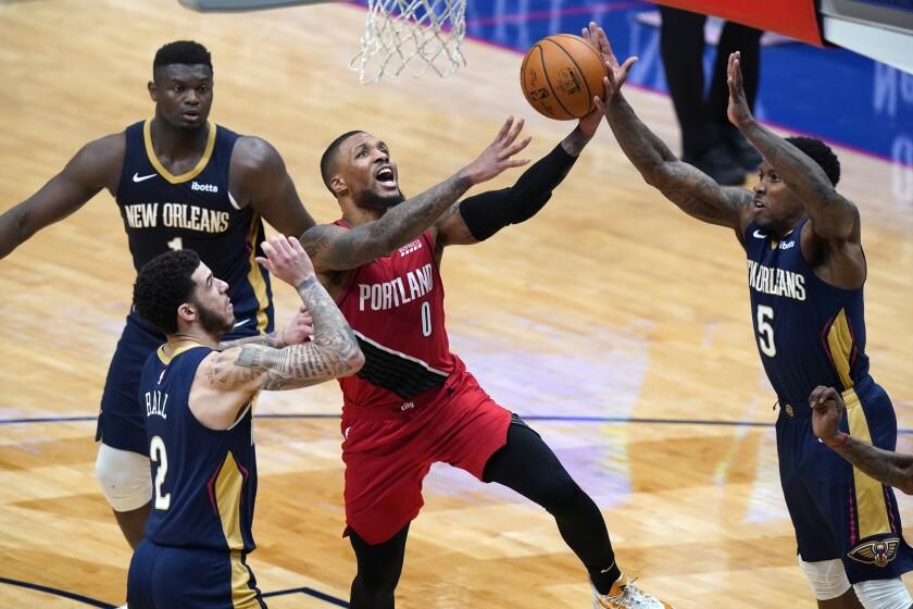 Portland Trail Blazers guard Damian Lillard goes to the basket between New Orleans Pelicans defenders.