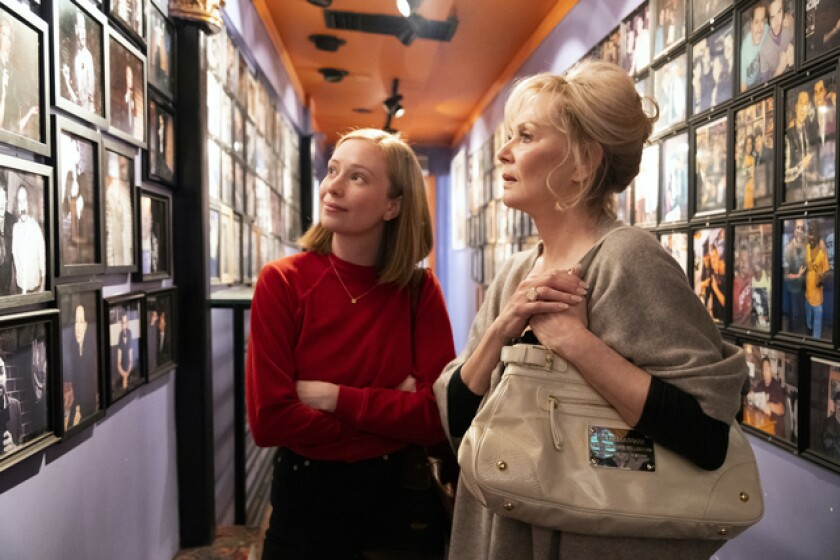 Two women look at photos on the wall of renowned comedy club