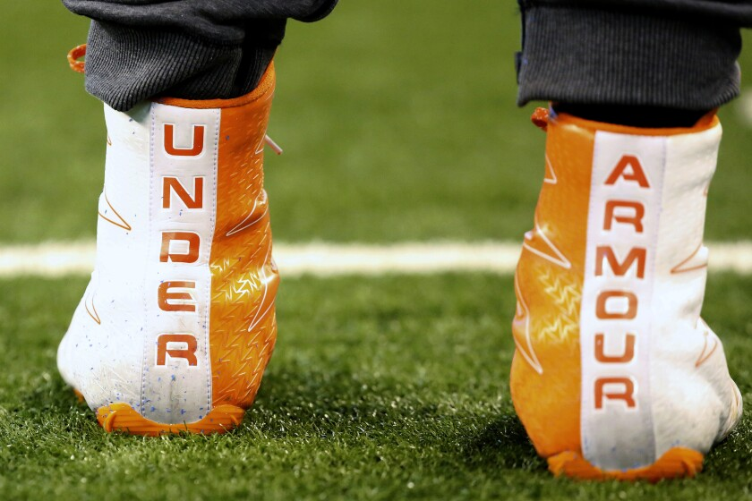 FILE- This March 5, 2017, file photo shows a closeup of Under Armour cleats are seen before a drill at the 2017 NFL football scouting combine in Indianapolis. Under Armour says it's considering a restructuring plan and anticipates the virus outbreak in China dragging first-quarter sales down by $50 million to $60 million. The athletic clothing company moved to a loss of 3 cents per share in the fourth quarter. Its adjusted profit was 10 cents per share, meeting the expectations of analysts polled by Zacks Investment Research. Revenue of $1.44 billion was below the $1.46 billion Wall Street predicted. (AP Photo/Gregory Payan, File)