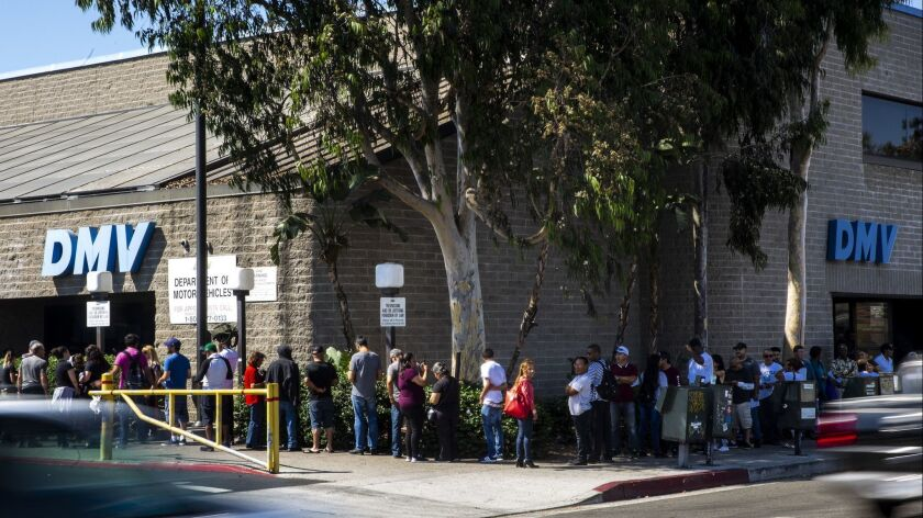 A line of people wait to be helped at a California Department of Motor Vehicles Office stretches around the building at the South LA location on Aug. 7, 2018.