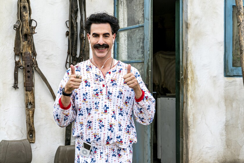 Borat gives two thumbs up while listening to an iPod