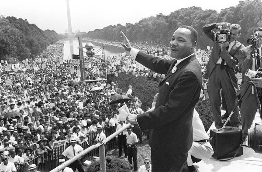 The Rev. Martin Luther King Jr., center, waves from the steps of the Lincoln Memorial to supporters on the Mall in Washington, D.C., on Aug. 28, 1963.