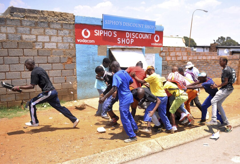 Looters make off with goods from a store in Soweto, South Africa, on Jan. 22.
